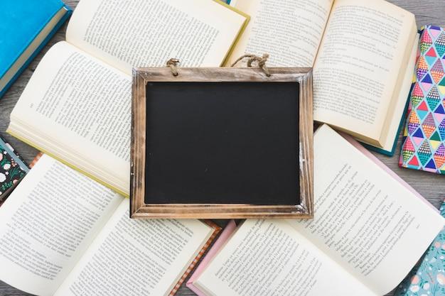 Ardoise vierge décorative sur les livres ouverts