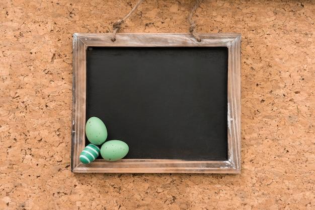 Ardoise vierge avec des oeufs verts pour le jour de pâques