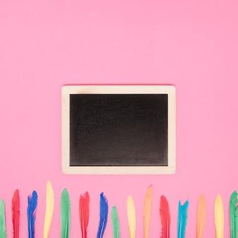 Ardoise vierge avec rangée de plumes colorées sur fond rose