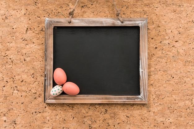 Ardoise vierge avec trois oeufs colorés pour le jour de pâques