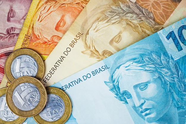 Argent brésilien et pièces de monnaie sur une table.