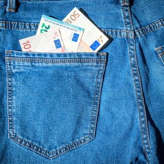 L'argent dans la poche de jeans bleus- concept de trésorerie en euros