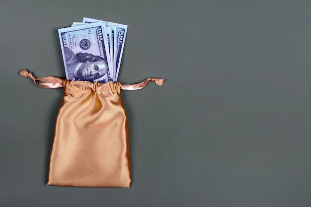 Argent dans un sac cadeau doré sur fond gris