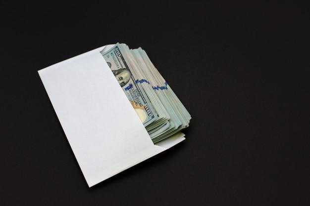 Argent dollar dans l'enveloppe sur fond noir