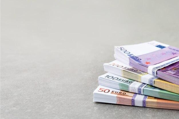 L'argent de l'euro. argent comptant, factures en euros. des piles de billets en euros sur fond de béton en cinq cents, deux cents, cent cinquante et cinquante. copyspace pour le texte.