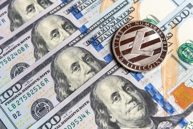 Argent litecoin crypto-monnaie sur les dollars américains. gros plan sur la crypto-monnaie numérique. echange, affaires, commercial. profitez de l'extraction de devises cryptées. mineur avec des dollars et une pièce de monnaie en argent litecoin.