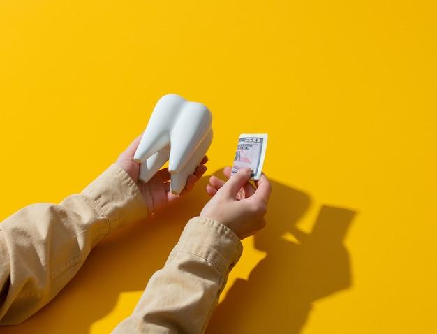 L'argent de la main féminine et la dent sur la surface jaune