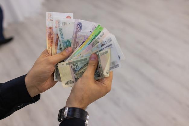 L'argent en main une personne raconte de l'argent roubles russes