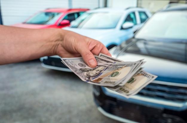 L'argent pour acheter la nouvelle voiture. notion financière. dollar en main