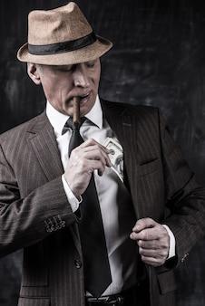 Argent et pouvoir. homme senior sérieux en chapeau et bretelles fumant un cigare et cachant de l'argent dans la poche en se tenant debout sur un fond sombre