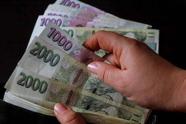 Argent tchèque dans les mains d'une femme sur fond noir. billets de 2000. couronnes tchèques dans un portefeuille noir.