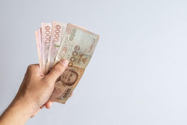 L'argent thaïlandais la main d'un homme sur fond blanc