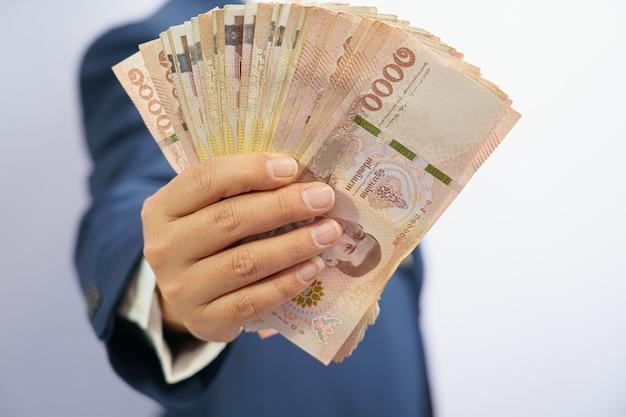 L'argent en thaïlande tenir en main l'homme d'affaires saisissant vêtu d'un costume bleu
