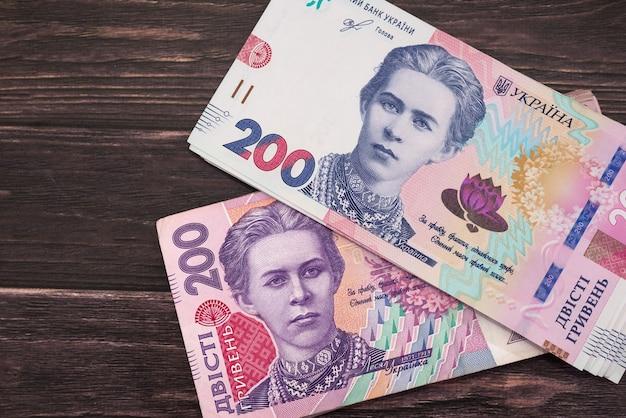 L'argent ukrainien sur un fond en bois. nouveaux et anciens billets de 200 hryvnia.