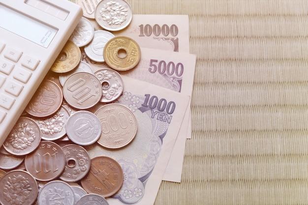 Argent, yen japonais, billets de banque, pièces de monnaie, calculatrice avec espace de copie