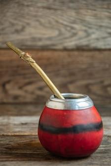 Argentine calebas pour mate, paille, courge citrouille, original sur une table en bois.