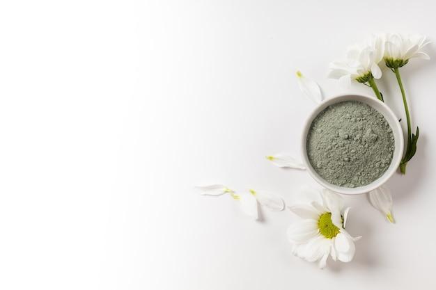 Argile bleue cosmétique sèche dans un bol de visage blanc avec des fleurs sur fond blanc
