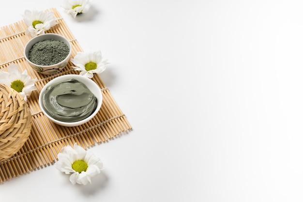 Argile cosmétique naturelle dans des bols et avec des fleurs sur un tapis de bambou pour salon spa