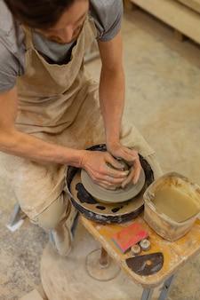 Argile avec de l'eau. un gars qualifié qui travaille dur, assis sur un banc en bois avec un tour de potier et s'occupe d'argile humide