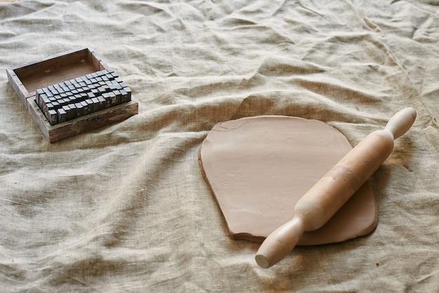 Argile roulée avec un rouleau à pâtisserie en bois sur la table