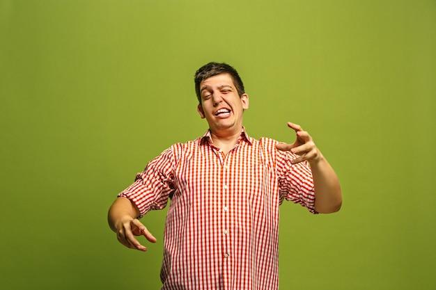 Argumenter, argumenter le concept. portrait de demi-longueur mâle drôle isolé sur fond de studio vert. jeune homme surpris émotionnel regardant la caméra