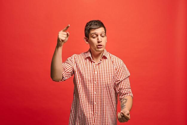 Argumenter, argumenter le concept. portrait de moitié drôle mâle isolé sur fond de studio rouge. jeune homme surpris émotionnel