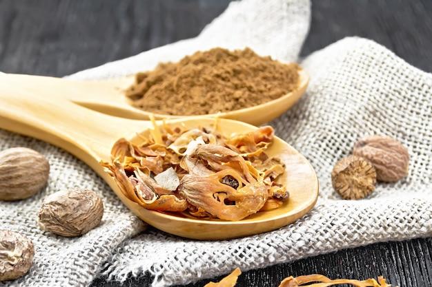 Arillus de muscade séchée et muscade moulue dans des cuillères, noix entières sur toile de jute sur fond de planche de bois