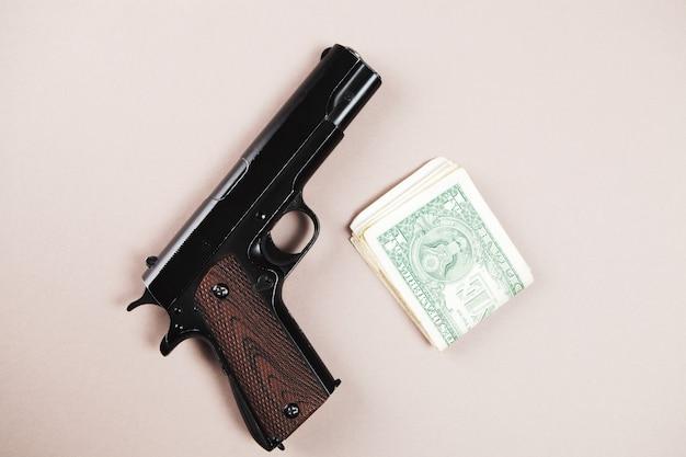 Arme à feu et argent sur la table. acheter des armes