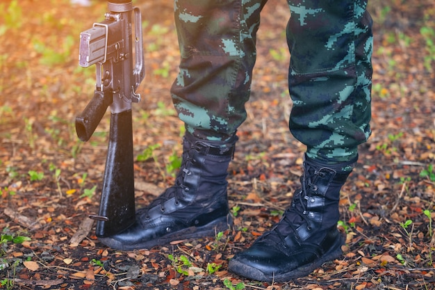 Arme à feu armée, bottes militaires lignes de soldats commando en uniformes de camouflage thaïlande