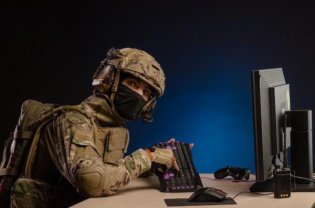 L'armée en uniforme assis devant un ordinateur mène une cyberguerre