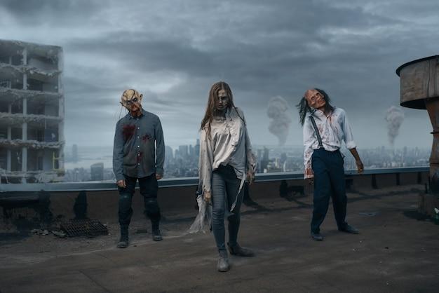 Armée de zombies effrayante sur le toit d'un bâtiment abandonné, poursuite mortelle. horreur en ville, attaque de bestioles effrayantes, apocalypse