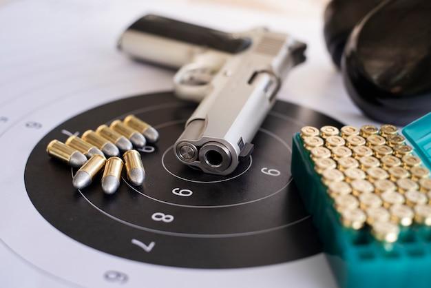 Armes à feu avec des munitions sur papier cible