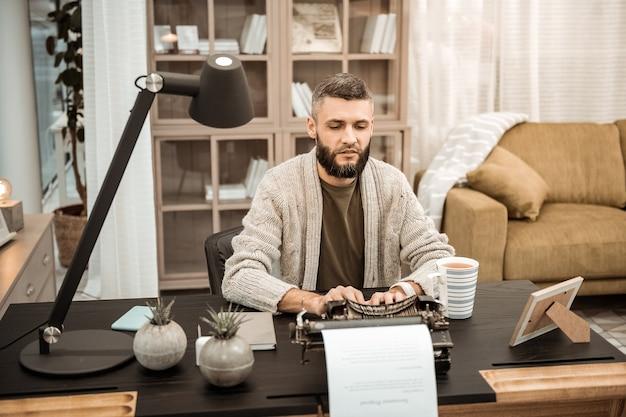 Armoire bien équipée. homme concentré sérieux en cardigan gris tapant sur une machine à écrire tout en passant du temps dans une armoire à la mode