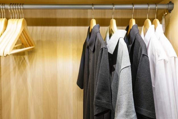 Armoire en bois dans le dressing avec des vêtements suspendus sur le rail