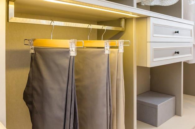 Armoire en bois moderne avec des vêtements suspendus sur le rail dans l'intérieur du placard