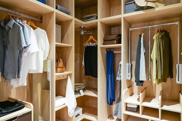 Armoire en bois moderne avec des vêtements suspendus sur le rail