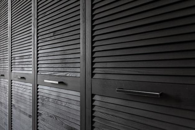 Armoire en bois noir décorée de stores, armoire avec décoration de stores.