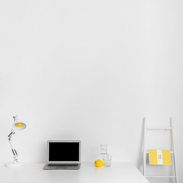 Armoire minimaliste en couleur blanche avec ordinateur portable et escalier