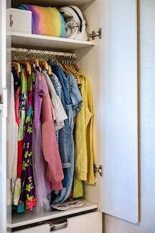 Armoire avec des vêtements d'ordre parfait nuances vêtements de rangement vêtements fille adolescente