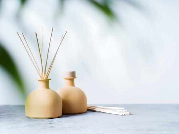 Aroma reed diffuseur parfum d'ambiance avec des bâtons de rotin sur un fond clair avec des feuilles de palmier.
