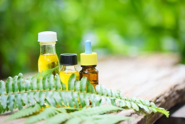 Aromathérapie arôme de bouteilles d'huile à base de plantes avec des feuilles de fougère formulations à base de plantes, y compris des fleurs sauvages et des herbes sur bois - huiles essentielles naturelles sur bois et feuille verte bio