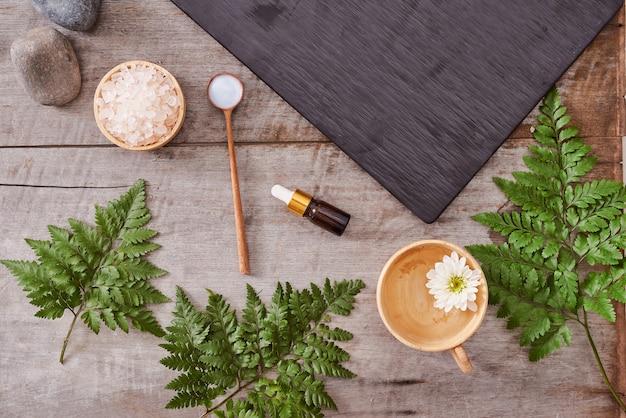 Aromathérapie : sel de bain, crème cosmétique, savon bio et congé vert sur table en bois