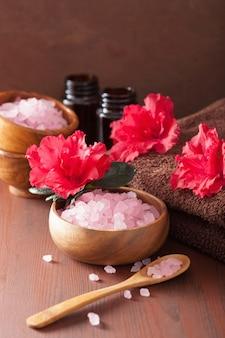 Aromathérapie spa avec des fleurs d'azalée et du sel aux herbes sur fond sombre rustique