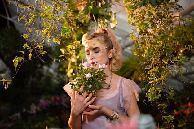 Arôme agréable. belle jeune femme tenant des roses tout en profitant de leur odeur