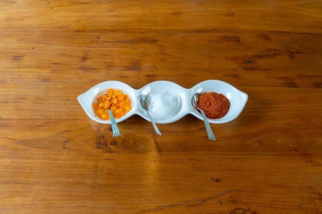 Arôme d'asie dans le petit bol blanc comme le sucre au vinaigre et le piment pour une sorte de nouilles à la thaïlandaise.