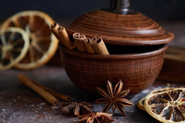 Arômes de vin chaud: cannelle, anis étoilé, peaux d'orange dans un bol brun