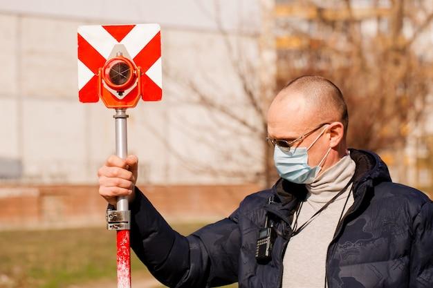 L'arpenteur détient un réflecteur géodésique dans un masque de protection
