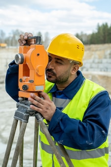 Arpenteur-géomètre en vêtements de travail et casque travaillant avec une station géodésique