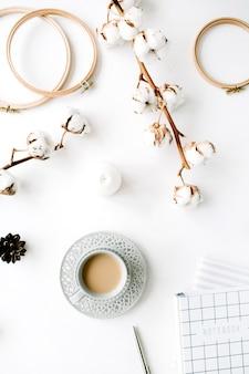 Arrangement d'accessoires féminins créatifs à la mode à plat avec café, branche de coton et agenda. branche de coton, cahier, tasse à café, cône de sapin sur blanc