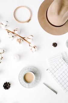 Arrangement d'accessoires féminins créatifs à la mode à plat avec café, branche de coton et agenda. chapeau, branche de coton, cahier, tasse à café, cône de sapin sur blanc